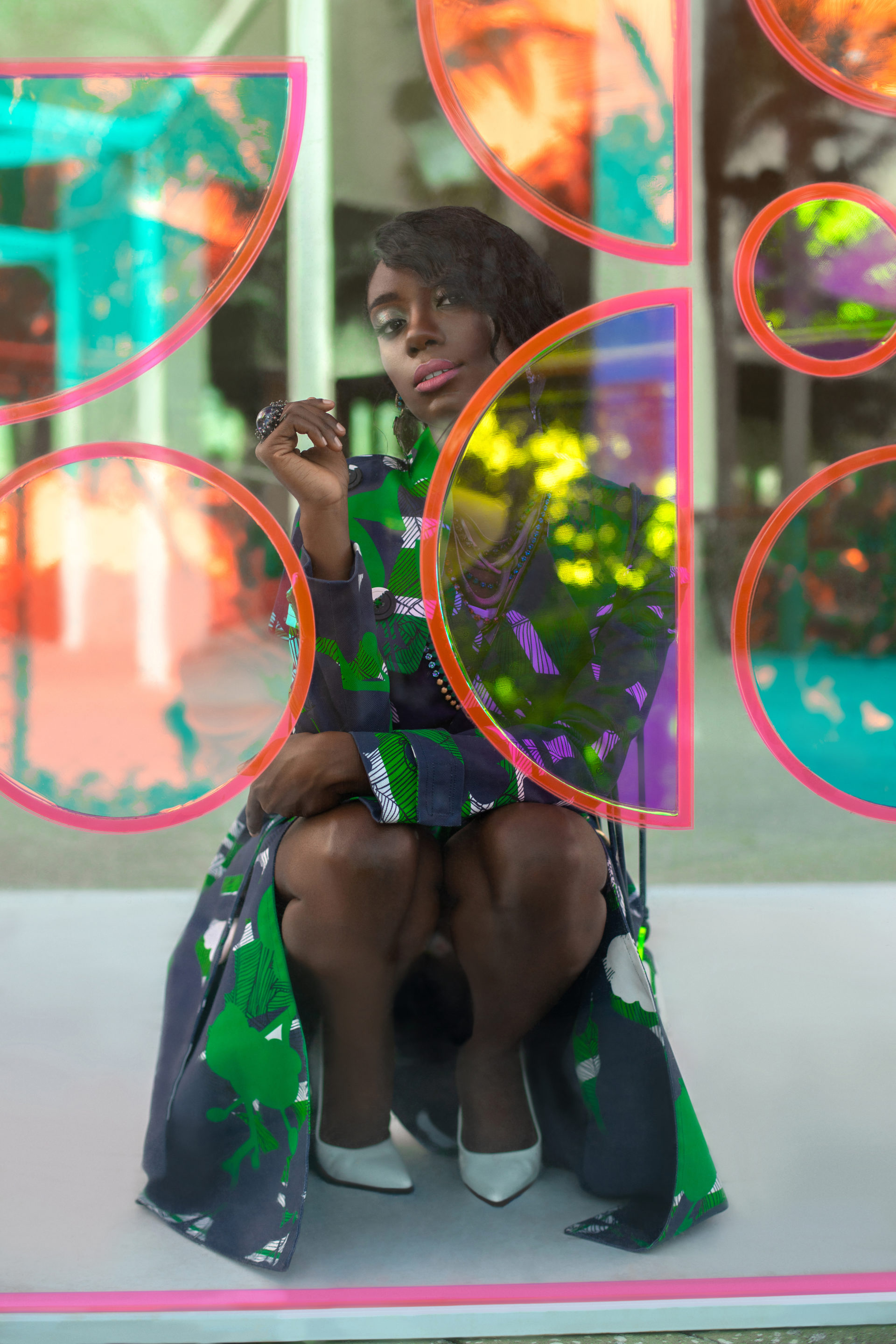 Young Black Woman In Green Dress Kneeling Behind Glass