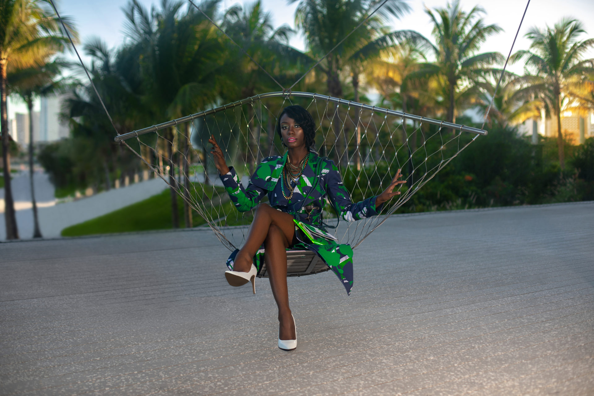 Young Black Woman In Green Dress Sitting In A Hammock
